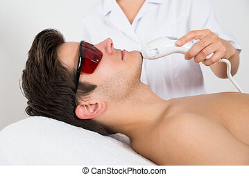 Young Man Receiving Laser Hair Removal Treatment At Beauty Center