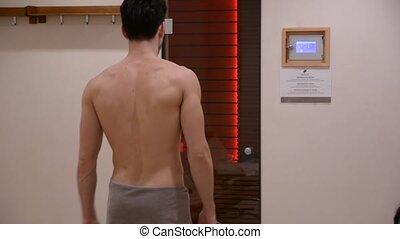 Young Man Relaxing in Sauna - Young Shirtless Muscular Man...