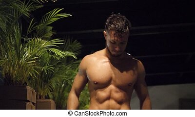 Young Man Walking Around Shirtless by Swimming Pool, Relaxing in Tranquil Setting at Night