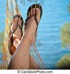 Young man relaxing on hammock at beach - Young man relaxing...