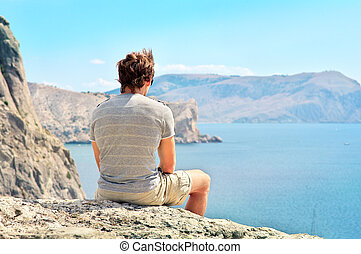 Young Man relaxing on rocky cliff sitting and looking on Sea and mountains Summer time Freedom concept