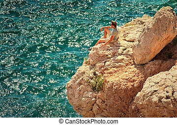 Young Man relaxing on rocky cliff with blue Sea on background Summer Traveling and Healthy Lifestyle concept