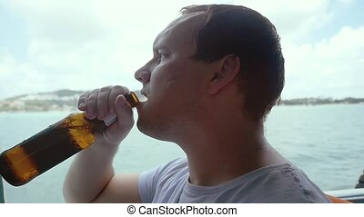 Young man relaxing on the vacation boat and drinking beerin...
