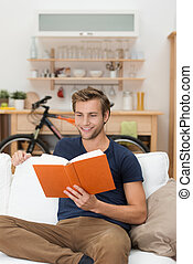 Young man relaxing reading a book