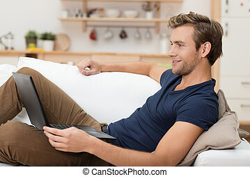 Young man relaxing with a laptop computer lying back on a...