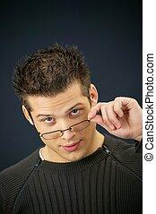 Young man removing his eyeglasses