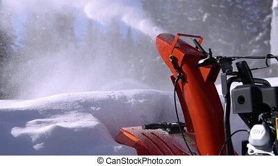 Very close up shooting of fresh snow being energetically shot in the air by the mouth of a bright orange mechanical snowplough in a sunny winter day.