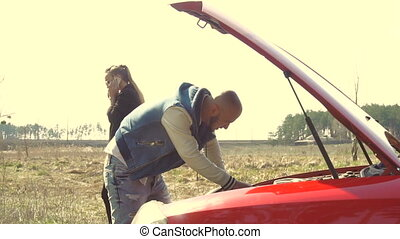 young man repair a car and his angry girlfriend talking phone in the field