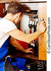 Young man repair something inside kitchen cabinet under the sink