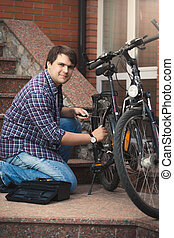 Young man repairing bicycle on porch of house