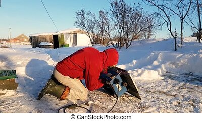 Young man repairing, circular saw, winter on the street, in the countryside