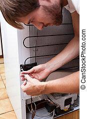 Young man repairing fridge