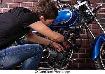 Young Man Repairing his Motorcycle Manually