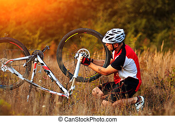 Young man repairing mountain bike in the forest - Bike...