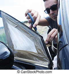 young man repairing the broken vent glass of a car