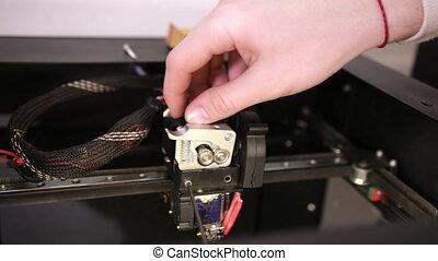 young man repairs 3D printer repairs the details of debugging work.