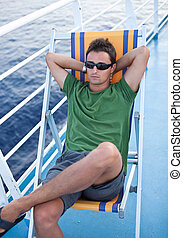 Young man resting on a deckchair while traveling on a liner...