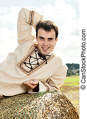 Young man resting on a haystack