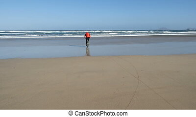 Young man rides a bicycle on a sand beach on Canary Islands towards waves of Atlantic ocean. Lanzarote