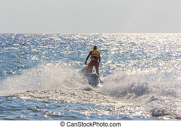 young man riding a hydrocycle in the sea