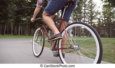 Young man riding a vintage bicycle at the park road. Sporty...