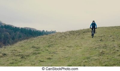Young man riding bicycle down the hill in autumn nature. -...