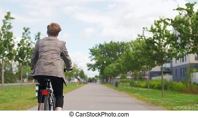 young man riding bicycle on city street - lifestyle, ...