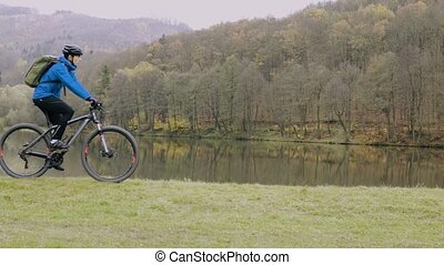 Young man riding bicycle outside in autumn nature.