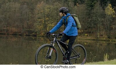 Young man riding bicycle outside in autumn nature. - Young...