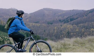 Young man riding bicycle up the hill in autumn nature. -...
