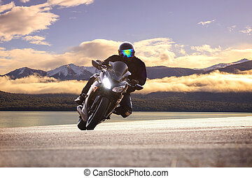 young man riding big bike motorcycle against sharp curve of asphalt high ways road with rural lake scene use for male adventure activities and motor sport hobby on holiday vacation