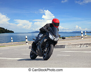 young man riding big bike motorcycle against sharp curve of...