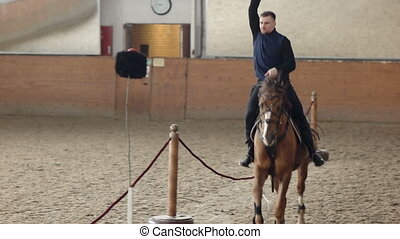 Young man riding his horse and swinging his sword. A Cossack...