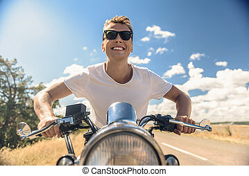 Young man riding his motorbike on open road - Live to ride,...