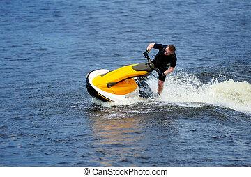 Young man riding jet ski - Young man riding yellow jet ski
