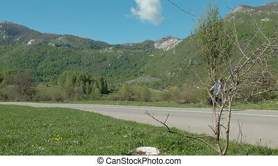 Young man riding longboard on country road on summer day outdoors.