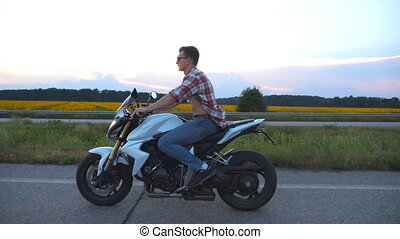 Young man riding on a modern sport motorbike. Handsome...
