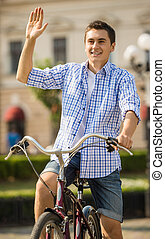 Young man riding on bicycle