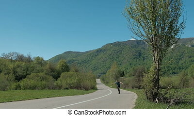 Young man riding on longboard on country road in summer day.
