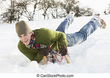 Young Man Riding On Sledge In Snowy Landscape