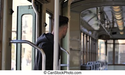 Young man riding on tram or old bus in city - Young handsome...
