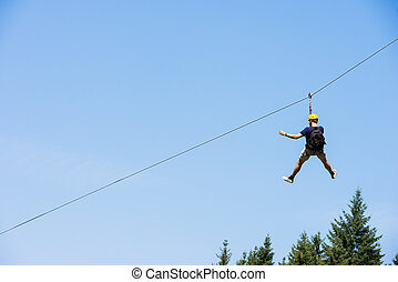 Young Man Riding On Zip Line - Rear view of young man riding...