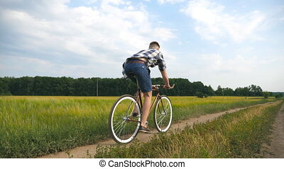 Young man riding vintage bicycle at the rural road over...