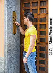 Young man ringing doorbell and talking on speaker phone