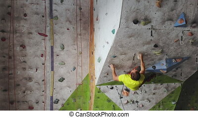 Young man Rock climber is Climbing At Inside climbing Gym....