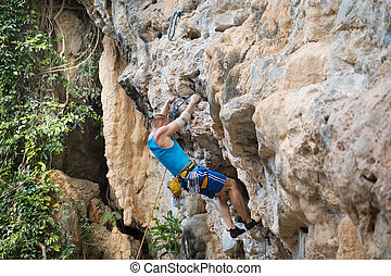 Young man rock climbing on white mountain