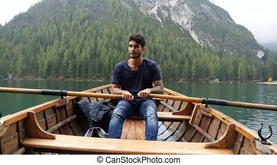 Young man rowing in boat on mountain lake - Young casual man...