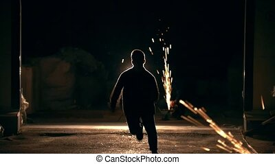 Young man run away through the sparks from grinder at night,...