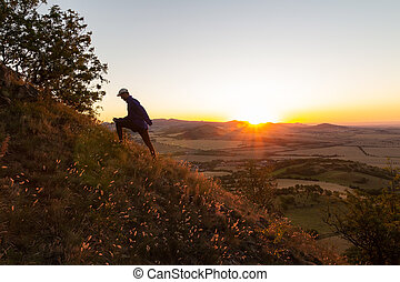 Young man runing up to hill in Czech central mountain valley at sunrise. Outdoor landscape