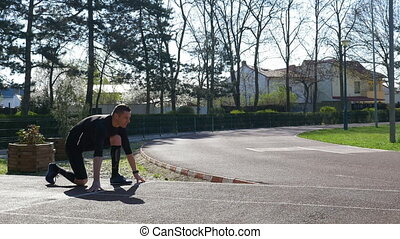 Young man runner at starting line in block start position on race track training in the park